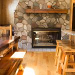 Northwoods Private Vacation Home view of stone fire place and dining area
